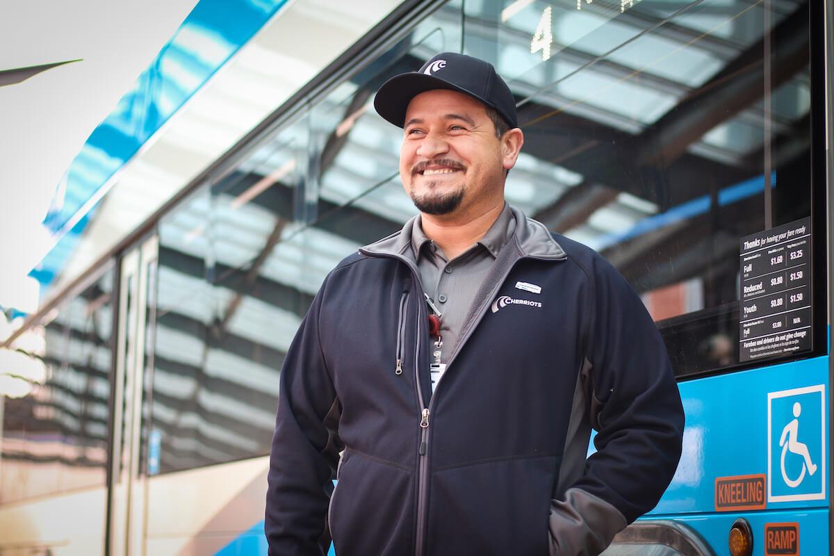 Cherriots employee smiling in front of bus