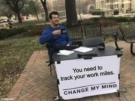 """Man sitting behind a table with a sign that says """"You need to track your work miles. CHANGE MY MIND."""""""