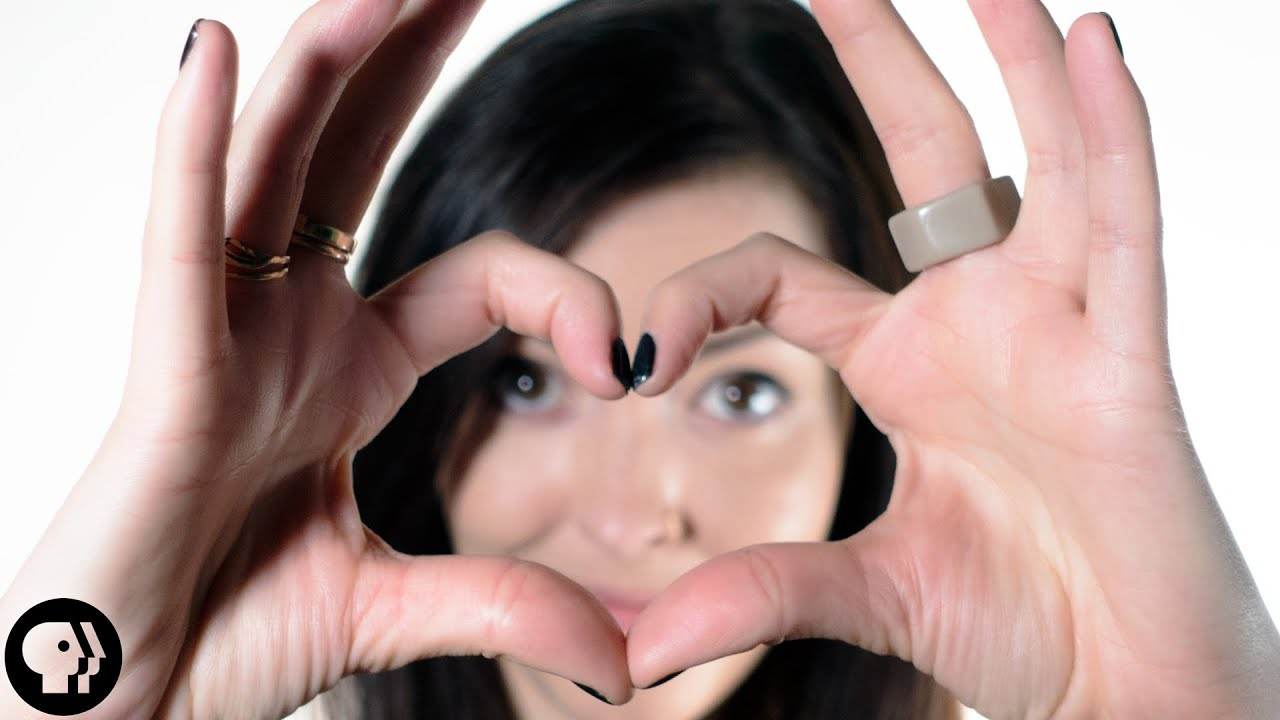 A Youtube thumbnail of a person smiling with their hands formed into a heart