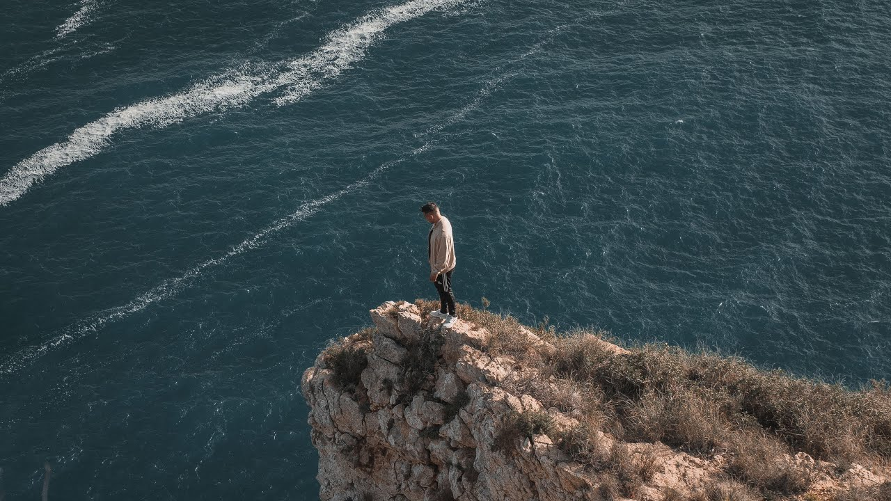 A Youtube thumbnail of a person on a cliff edge looking over the sea