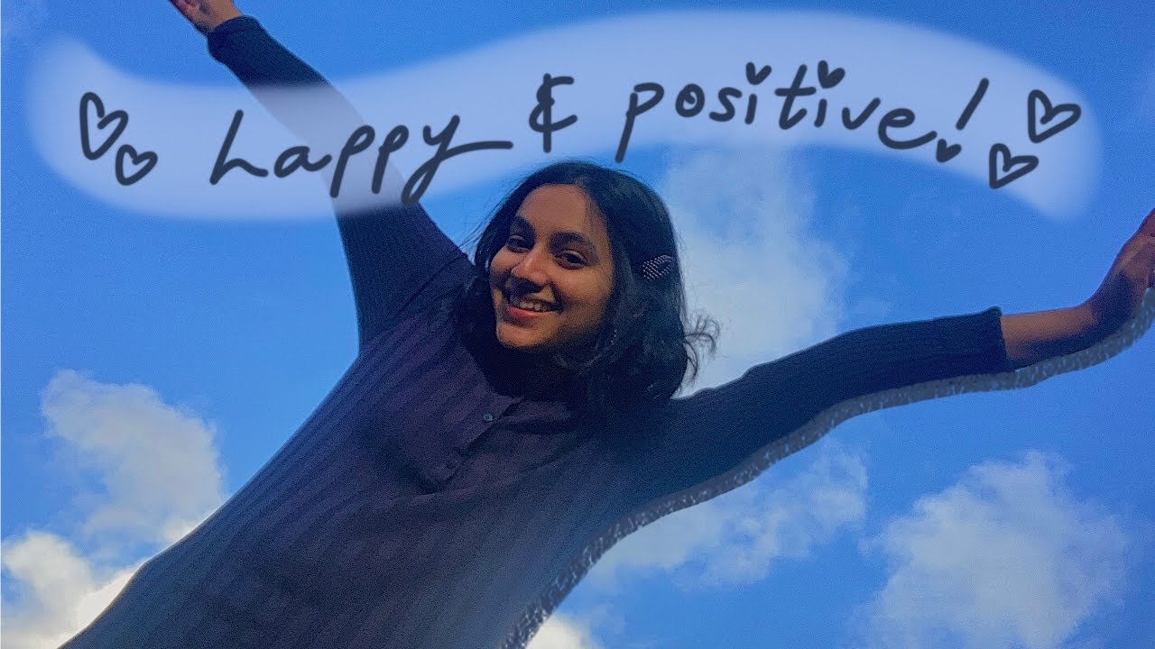 """A Youtube thumbnail of a person smiling and the words """"Happy & positive"""""""