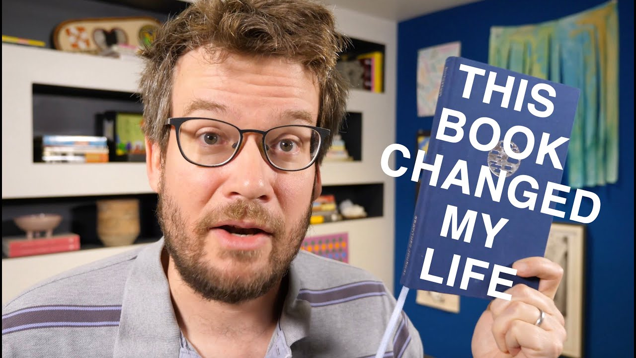 A Youtube thumbnail of a person holding a book and the video title