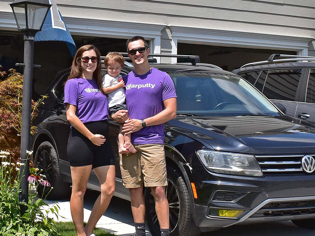 Smiling family standing next to vehicle they purchased with car financing from Carputty | Carputty