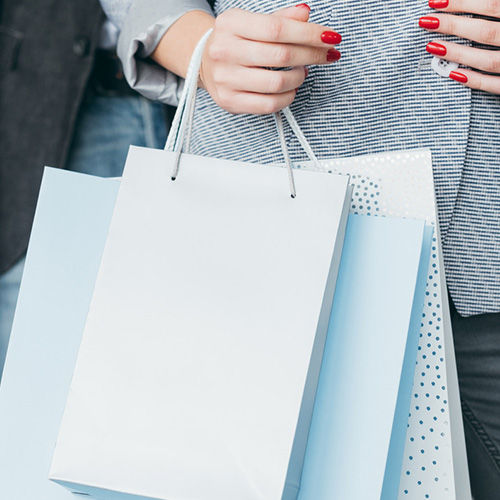 A lady holding several white shopping bags