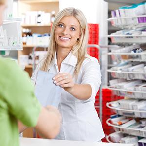A pharmacist handing a prescription to a customer