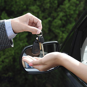 A man handing car keys to a woman