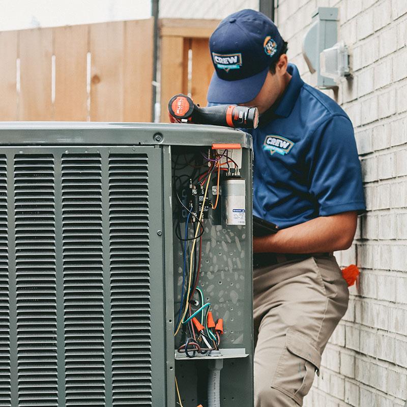 A Crew Home Service technician repairing a HVAC pump.