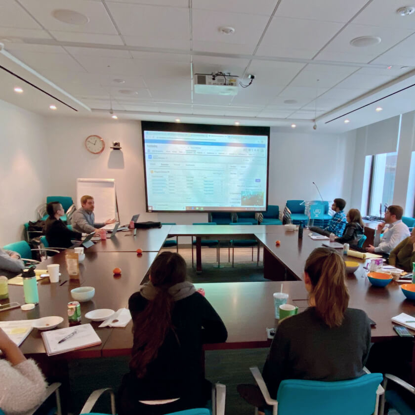 Image of team in meeting room viewing projector screen