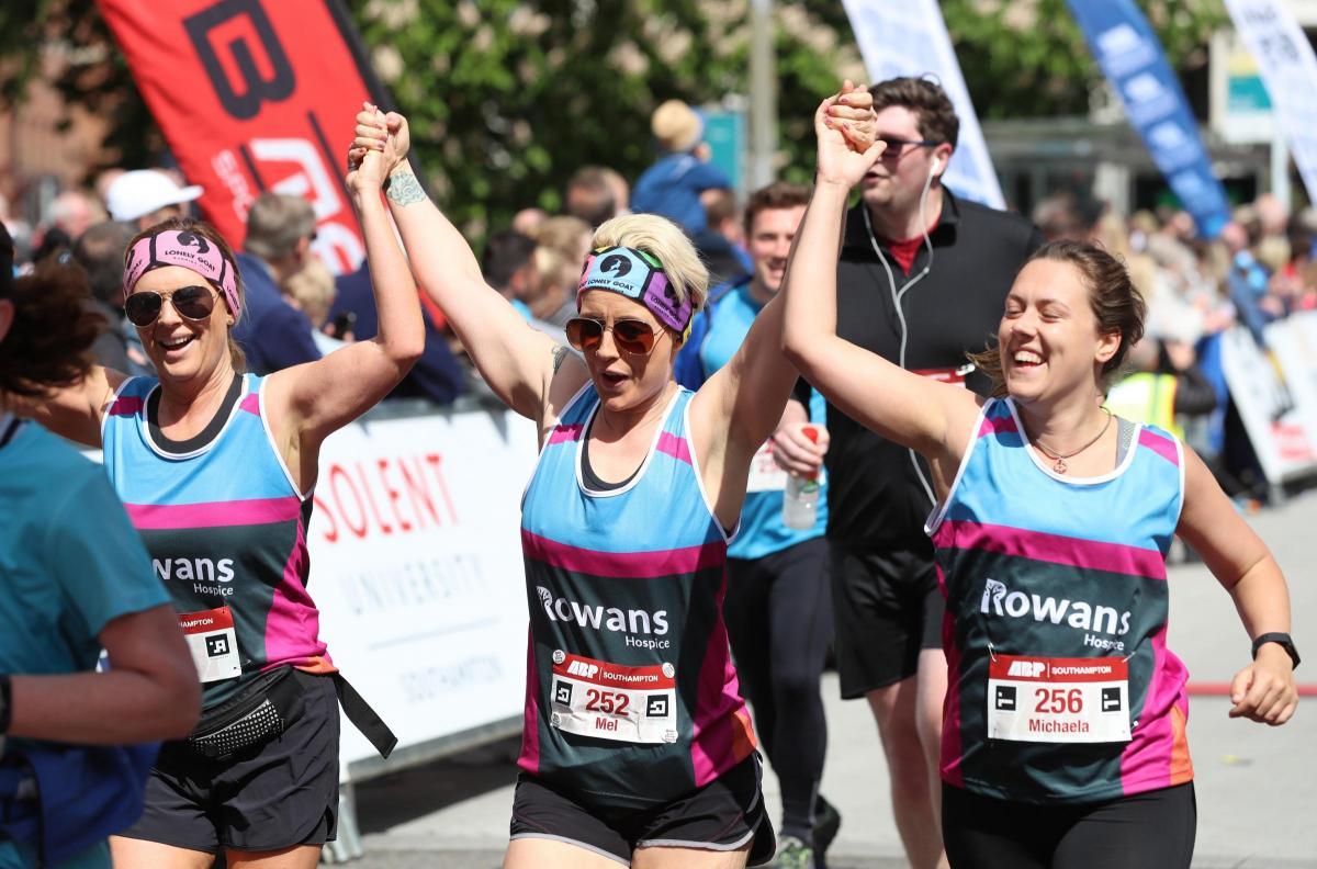 3 ladies finishing a marathon crossing the finish line