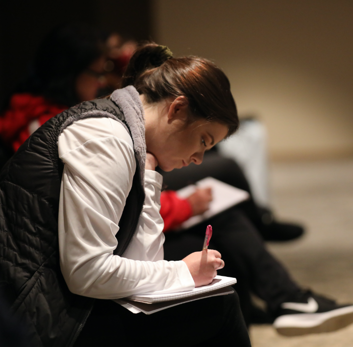 young adult taking notes