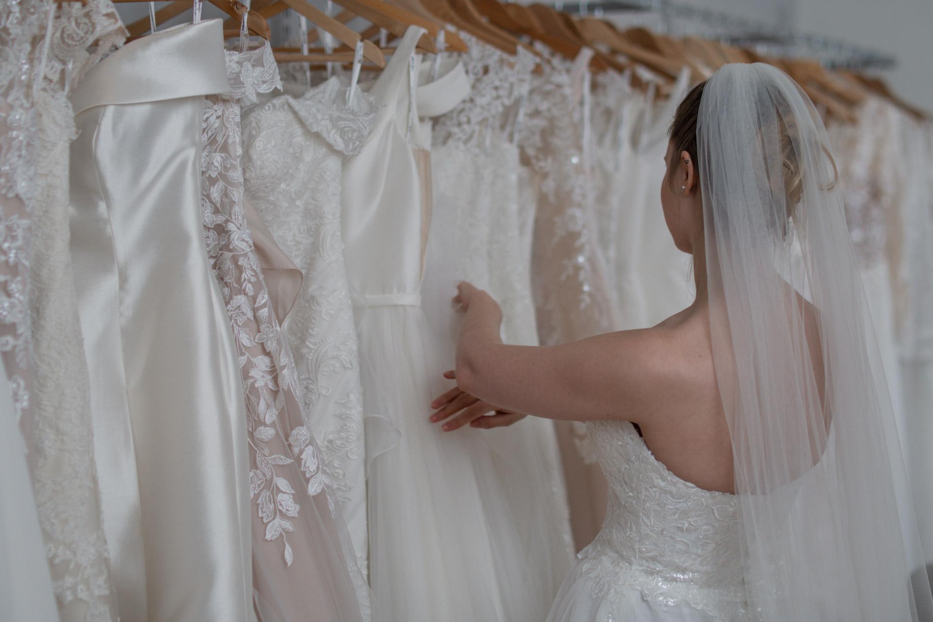 Brud leter gjennom kjolene på hengerene