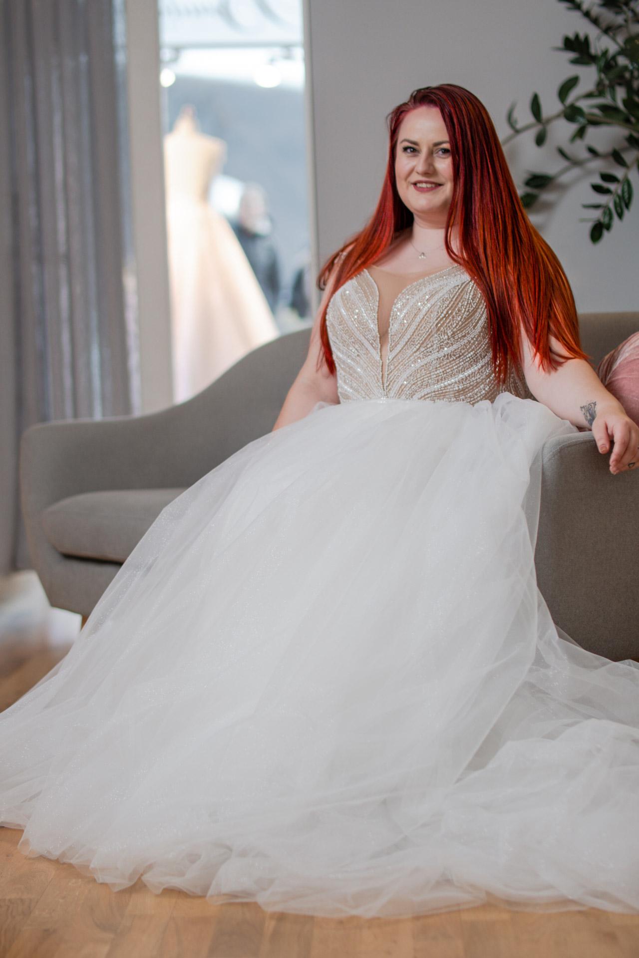 Brud i brudekjole sitter på sofaen