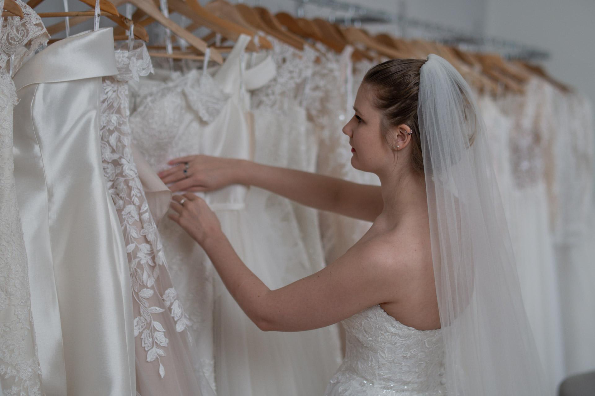 Brud blar gjennom kjolene i butikken til Brudehuset Tromsø