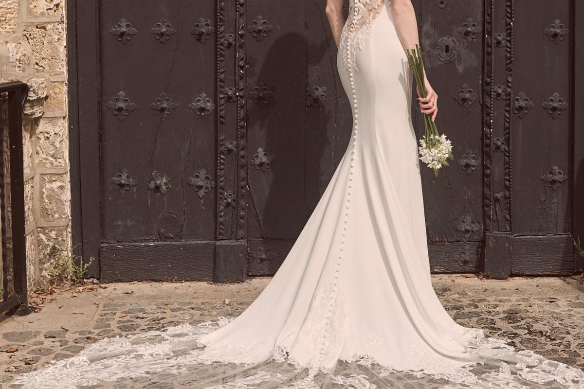 Model viser frem bryllupskjole utendørs. Kjole fra Maggie Sottero.