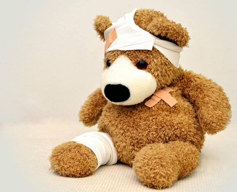 teddy bear with bandage on head and leg after getting treated in healthcare system