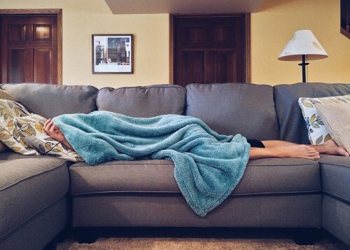 person laying on couch feeling ill