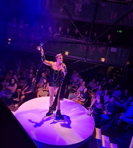 Reuben Kaye on stage holding drink and microphone