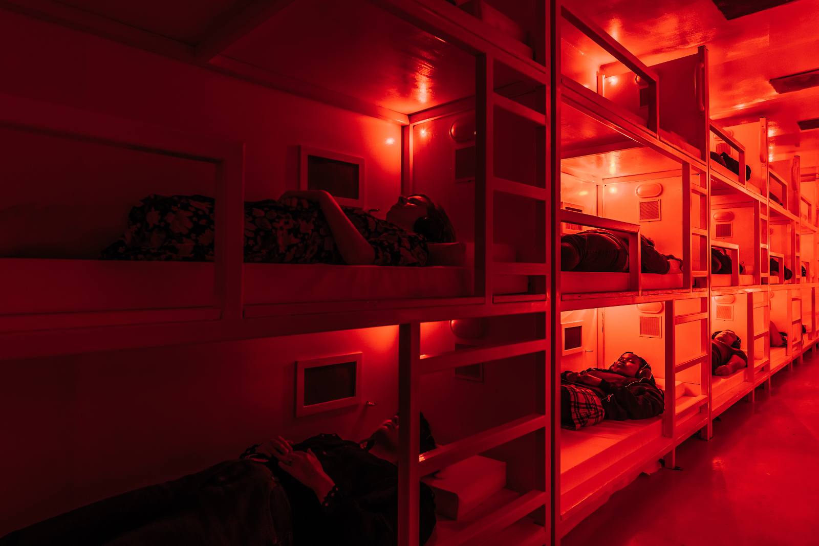 participants laying in bunkbeds in shipping container