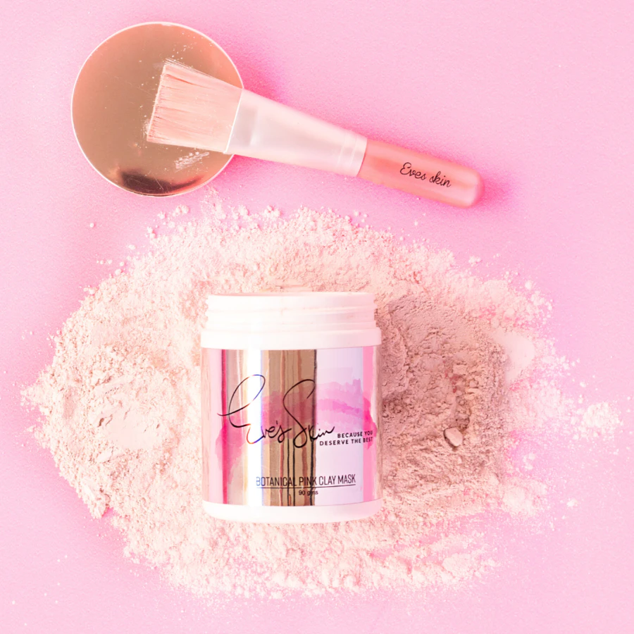 pink background with pink clay mask in pot and face brush