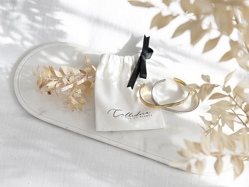 gold and silver cuffs displayed on marble tray with floral accents
