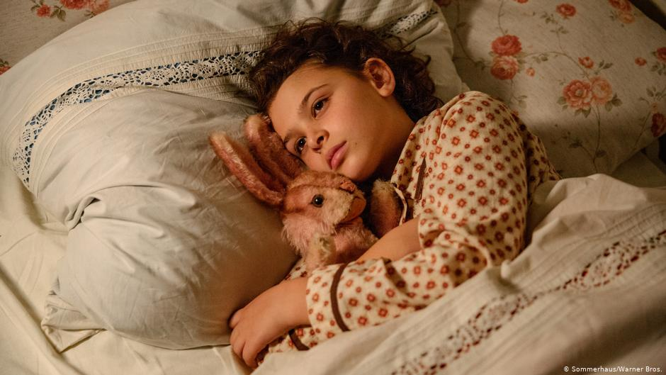image of girl laying in bed holding rabbit, still from movie