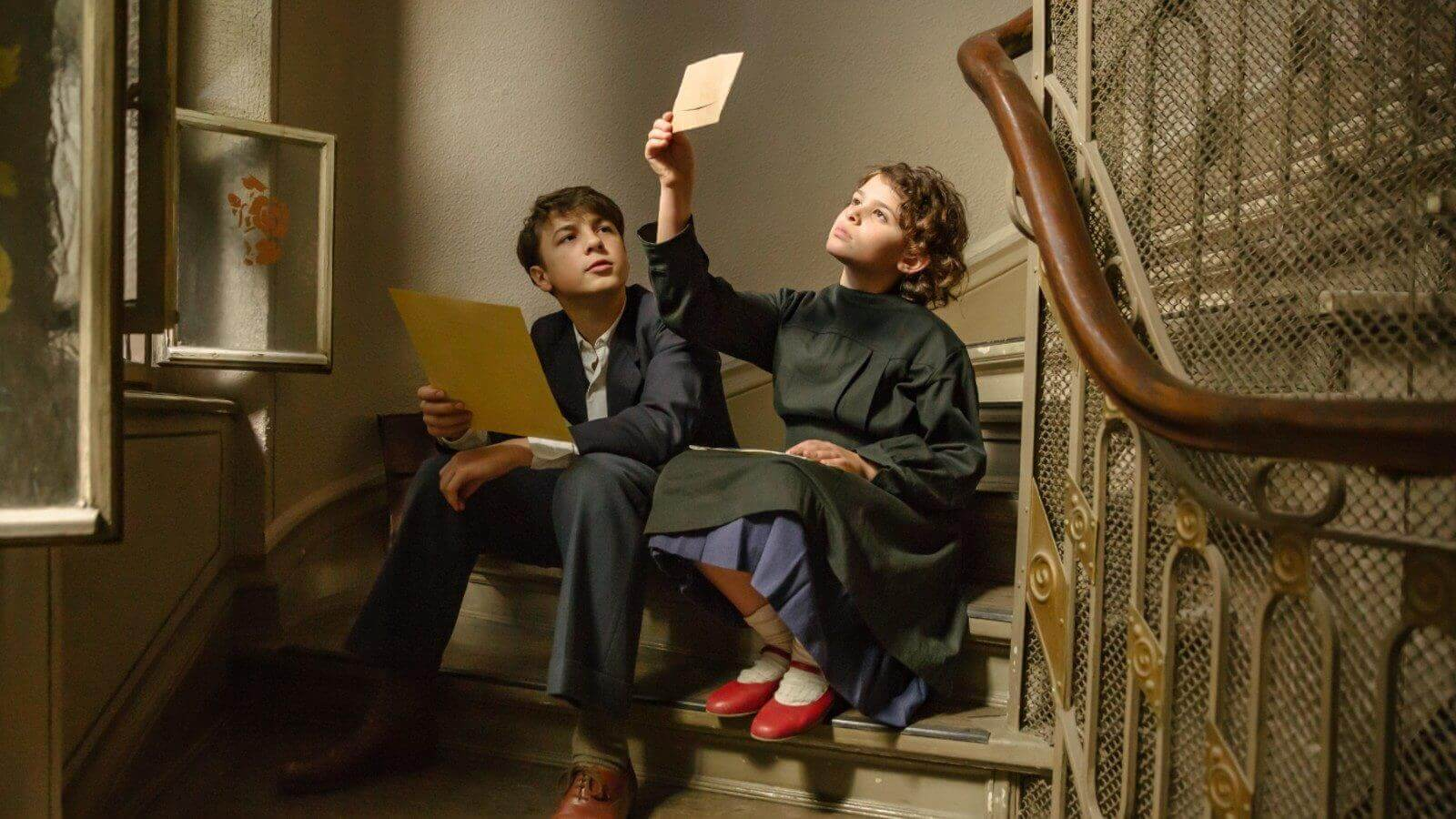 still from movie, wo children looking at papers