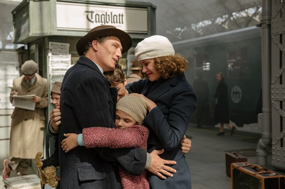 family embracing at train station