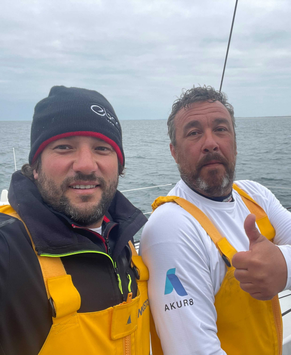 Antoine Cornic and Jean-Charles Luro on the boat, showing the Akur8's logo on their shoulders.