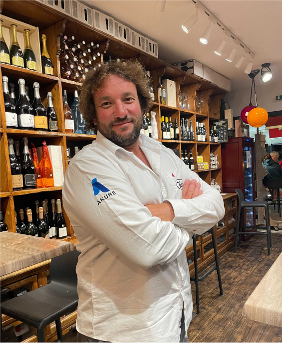 Antoine Cornic in his bar. In the background, the shells are loaded with lots of bottles of alcohol.