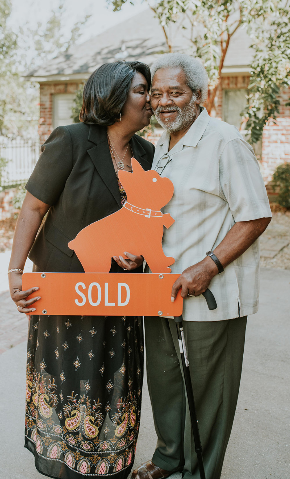 couple holding next home sold sign