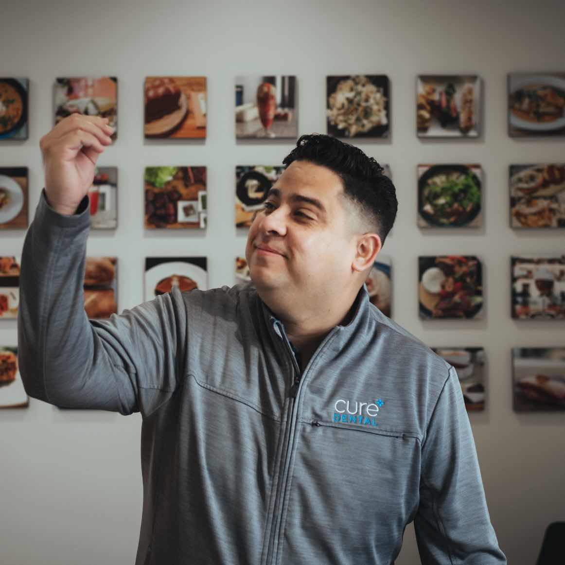 Photo of Dr. Shipley standing in front of a wall of food photography with his hand raised