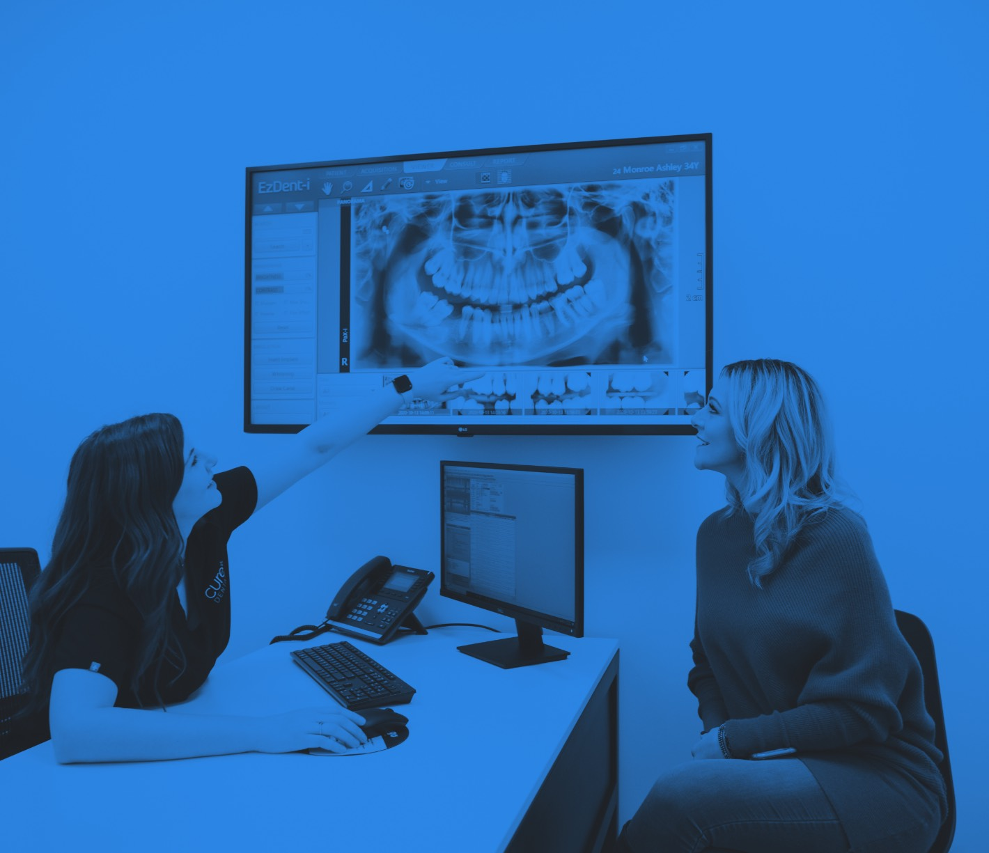 Photo of a team member and a patient looking at a dental scan on a large monitor