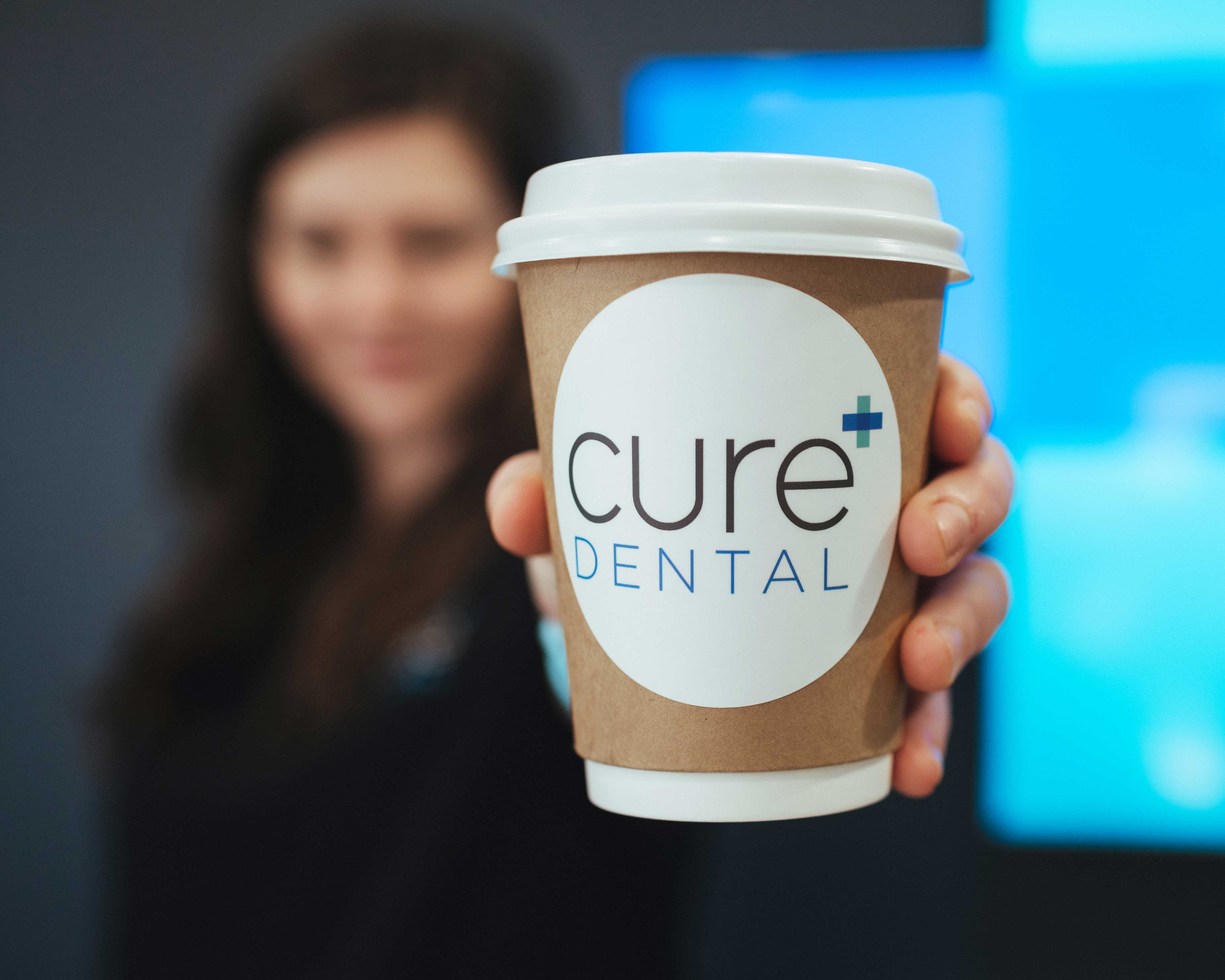 Photo of a team member holding a Cure Dental coffee cup
