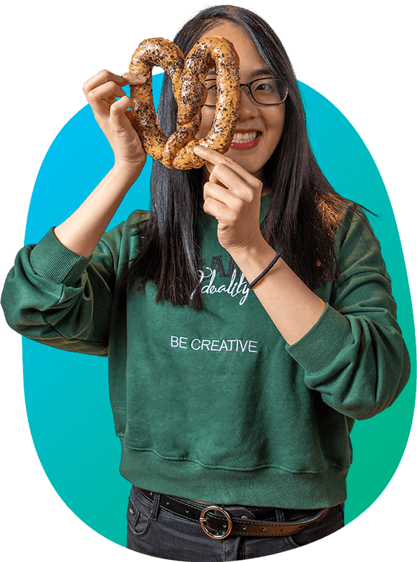 Woman wearing a green sweater and holding a large pretzel covering half her face