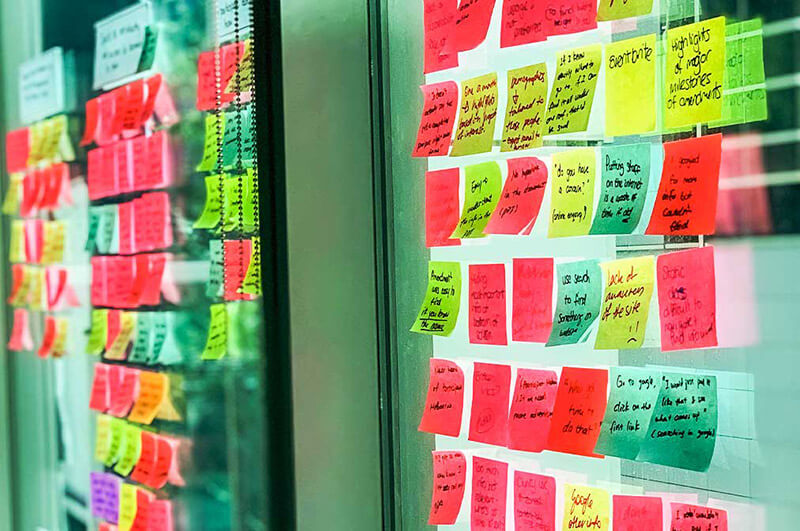 angle shot of yellow and pink post-it notes on a window
