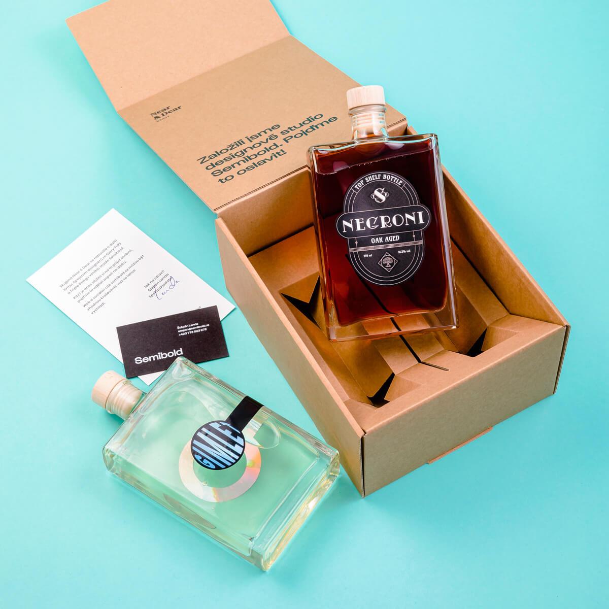 Otevřená krabice s koktejly, dopisem a vizitkou