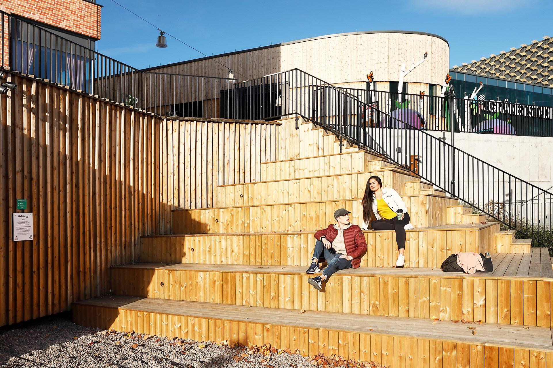 Bild på två personer som njuter av solen i en trappa