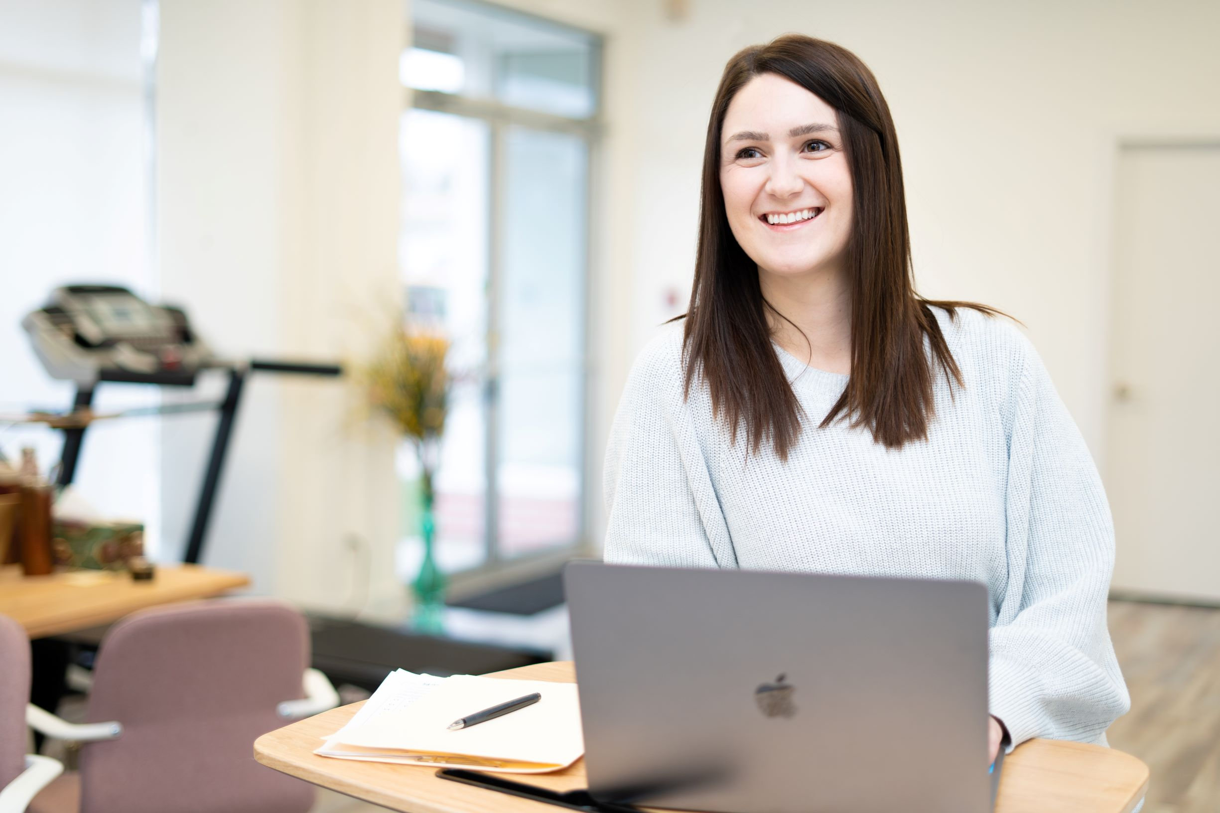 Smiling occupational therapist with open computer engaging with clients