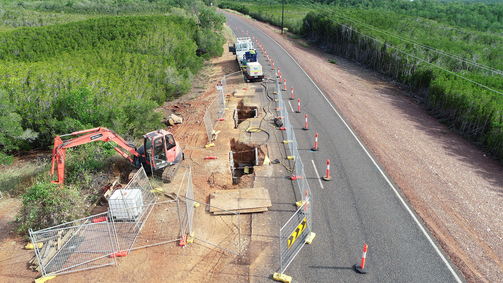 Workers drilling on the side of a road