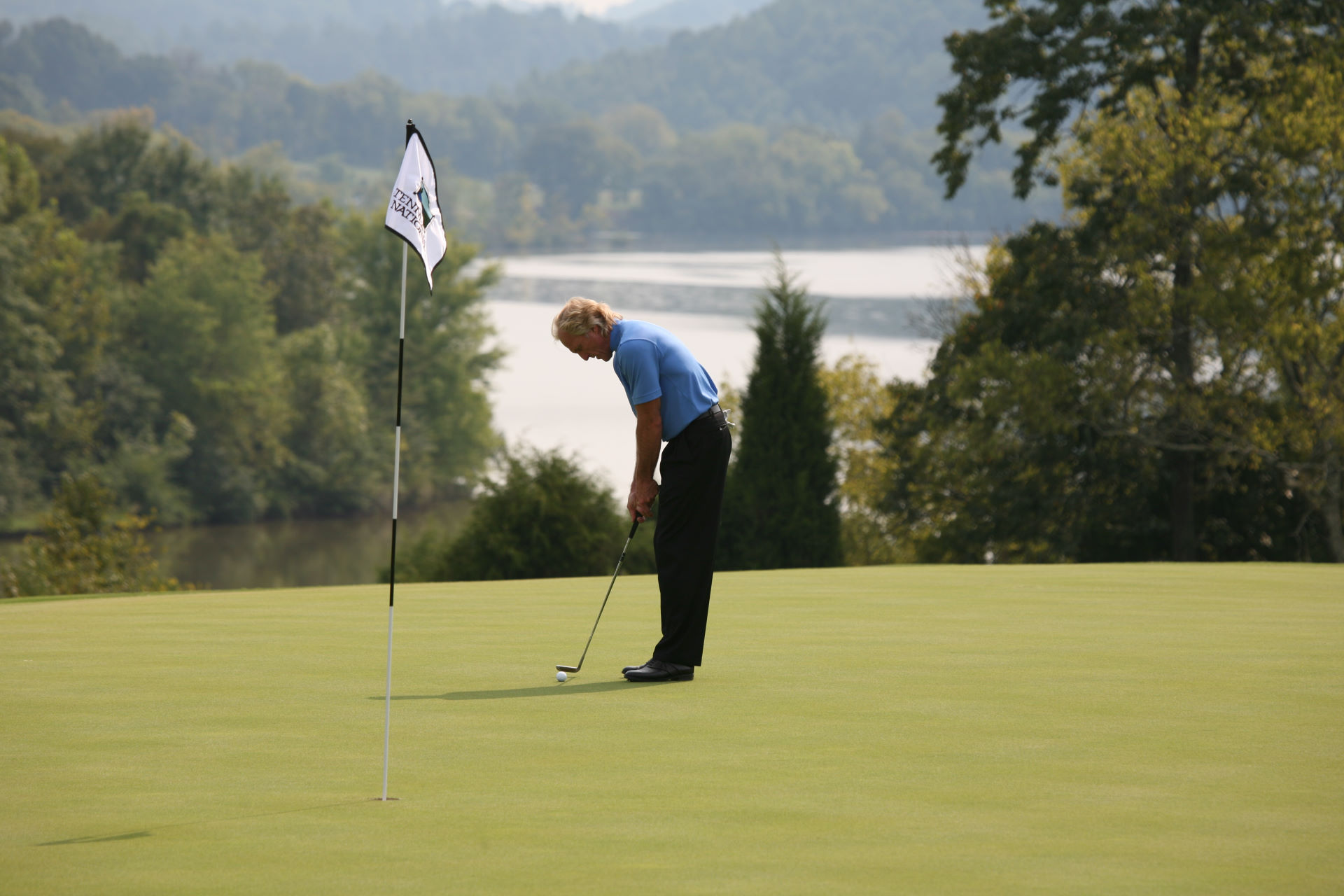 Greg Norman golfing at Tennessee National with Lake in Background