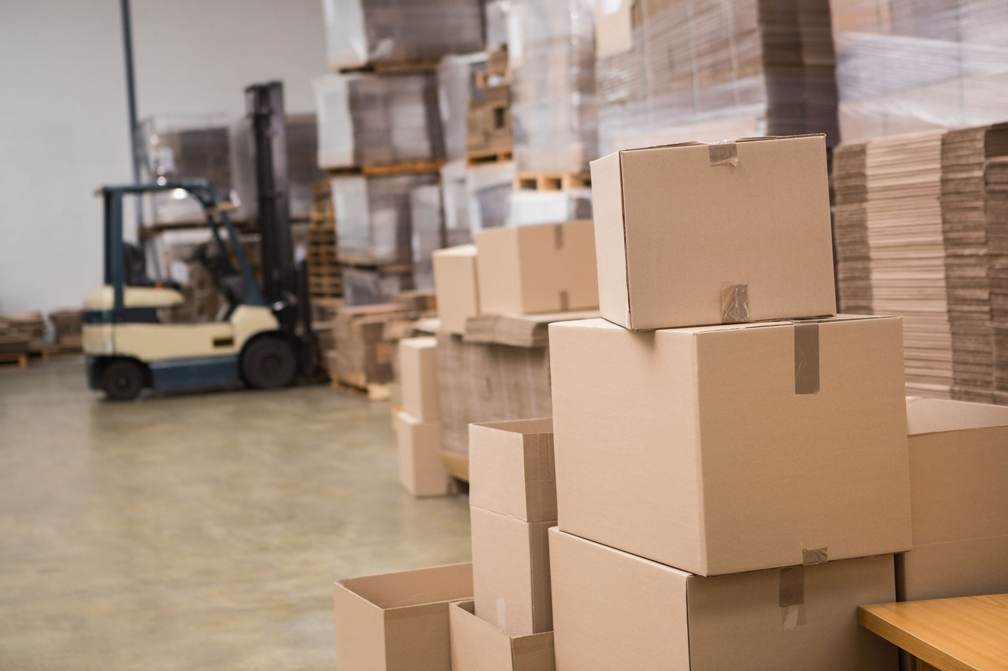Boxes in a warehouse being moved by a forklift truck