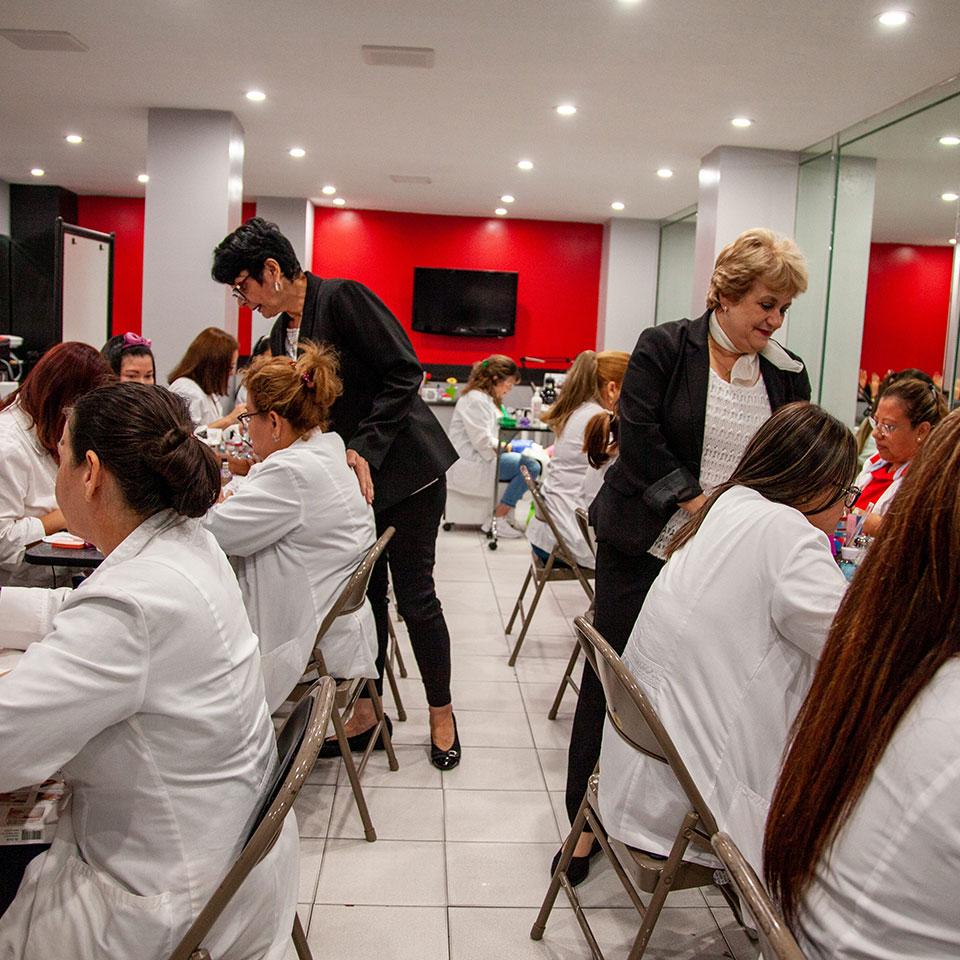Profesoras de Nouvelle Insitute enseñando manicura a un grupo de estudiantes.
