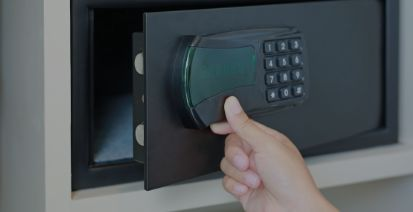 A hand inserting a key into a safe lock.