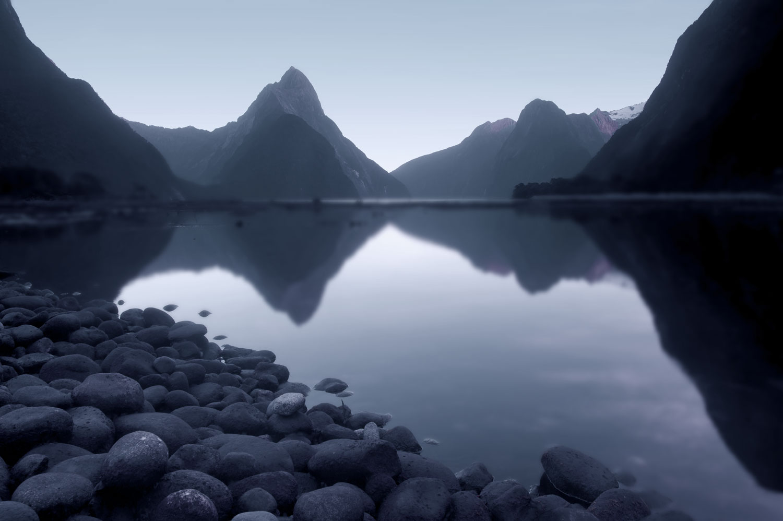Ein ruhiger See mit Kiesstrand, umgeben von Bergen.