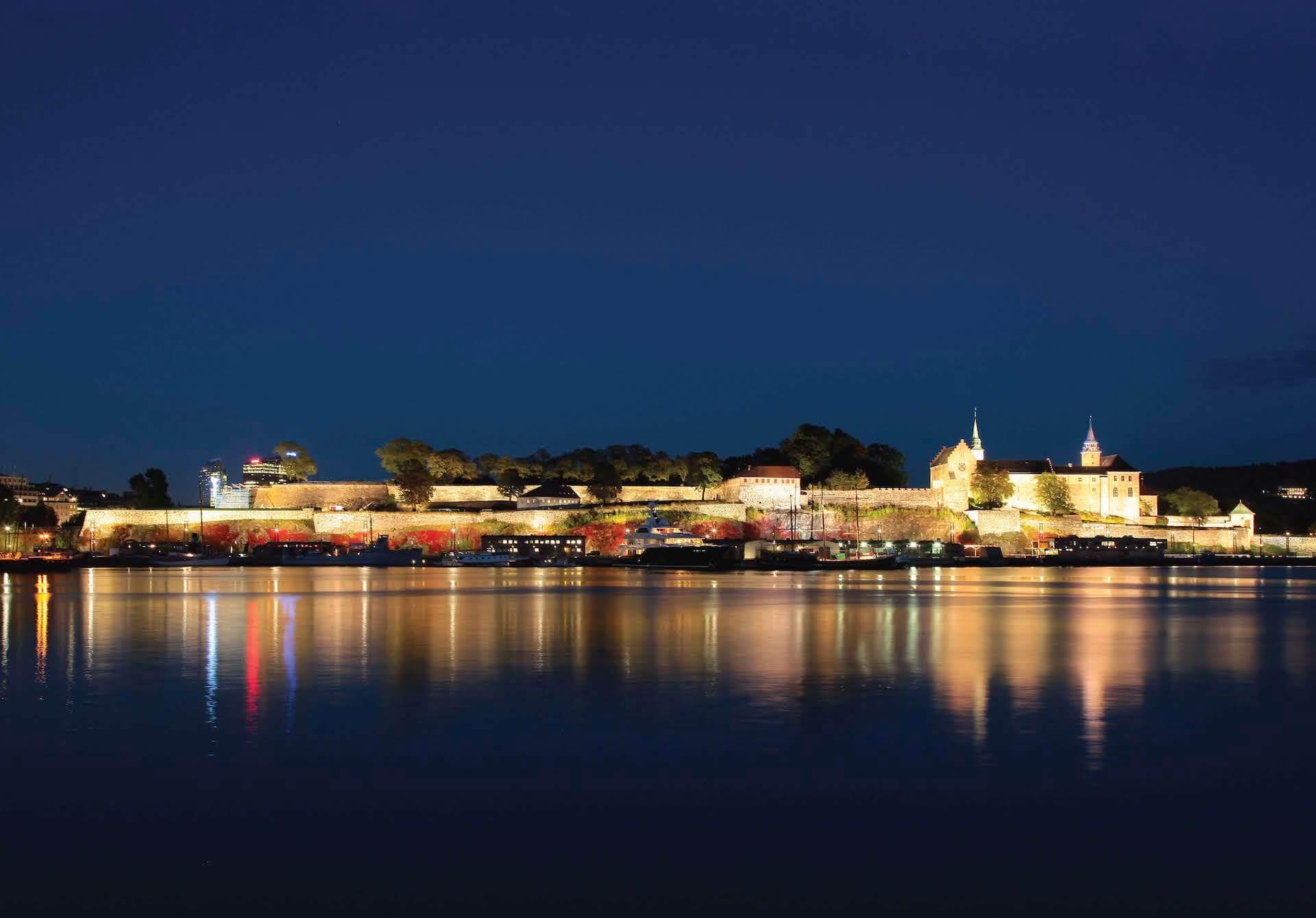 Akershus Festning lyser om natten sett fra sjøen.