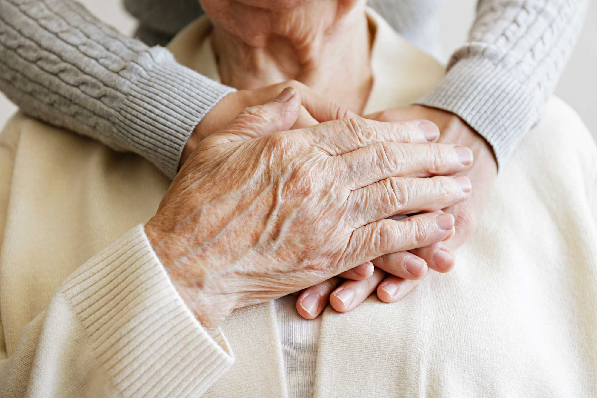 Hands are shown wrapped around an older person