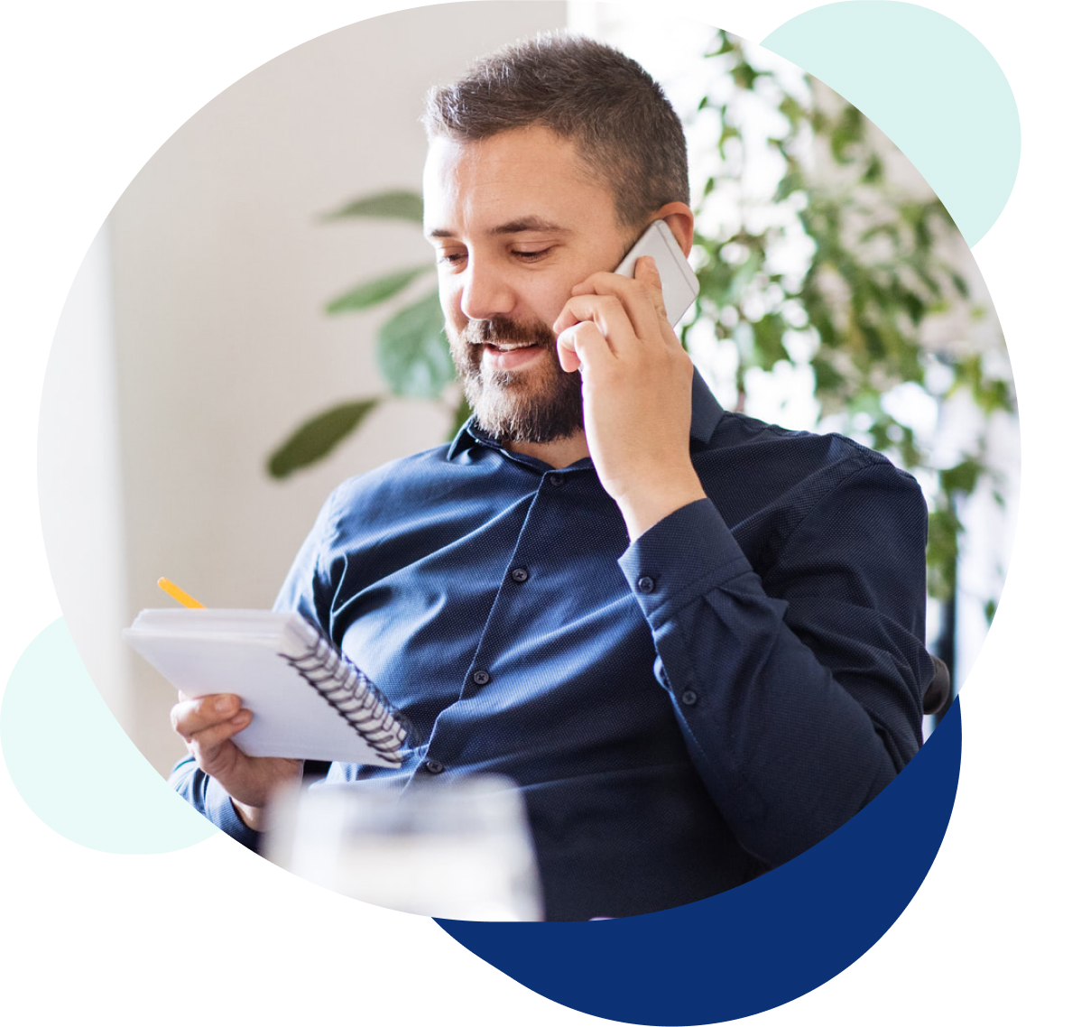 Man with beard on the phone at his office desk looking at notepad