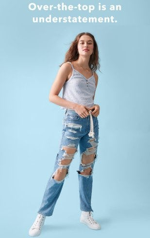 light blue background with a model with curly blonde hair wearing distressed light wash jeans and a white tank top with three buttons