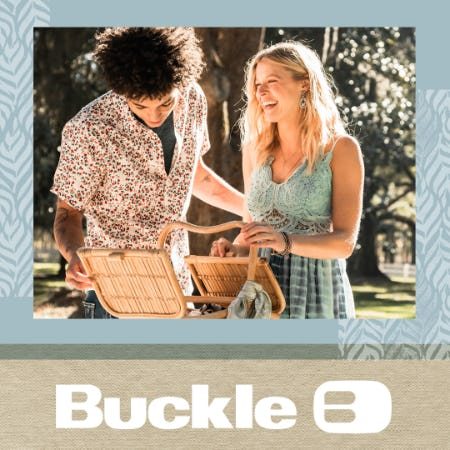 A man leaning over a picnic basket with curly brown hair and a white and red flowered spring shirt with a grey undershirt and a woman with blonde hair wearing a lace teal dress opening the picnic basket and laughing.