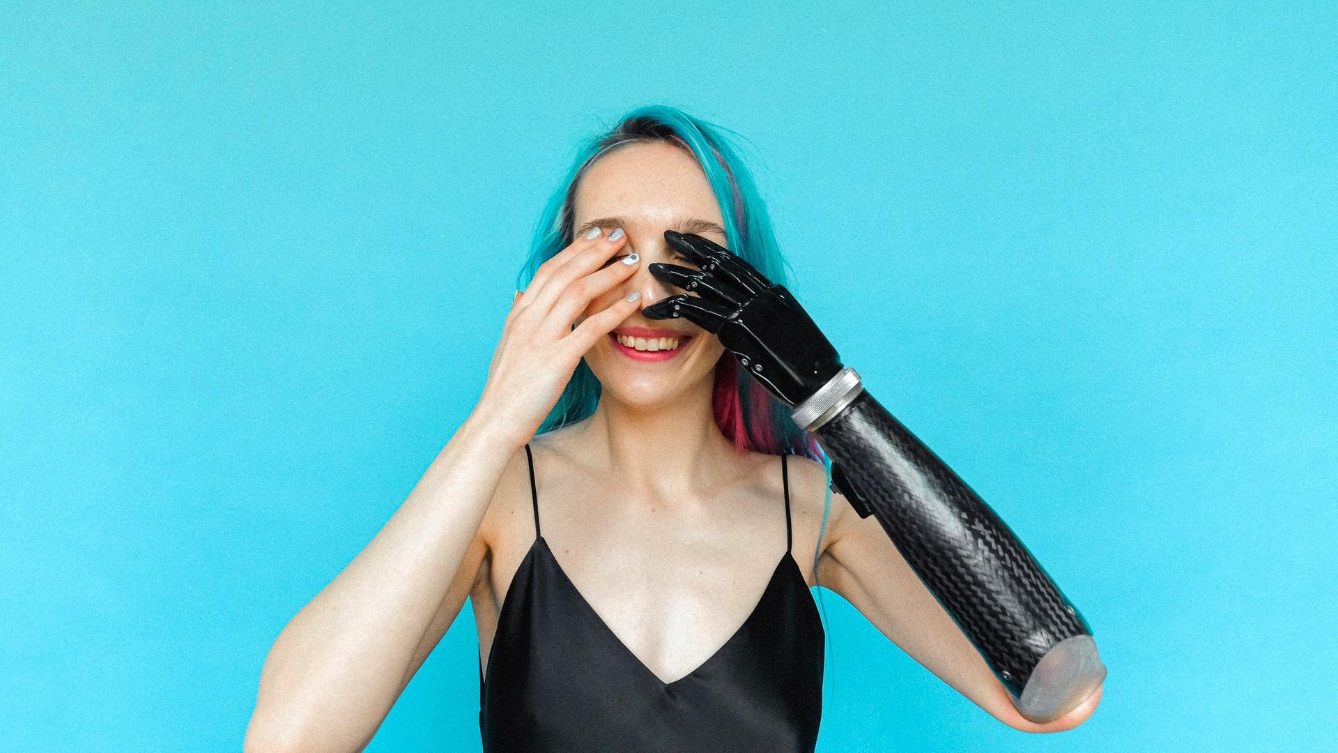 Kvinnan på bilden ler och håller för sina ögon, ena handen är en robotprotes. Hon har ljus hy och färggrannt blått / rosa / lila hår och bär ett svart tunt linne.